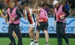 Andrew Wallis and Tim Barbour assisting player Jack Lonie in a St Kilda FC match last year.